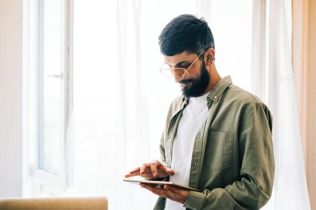Retrato de um empresário caucasiano usando computador tablet, trabalhando online.