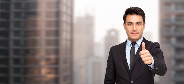 Retrato de um empresário charmoso vestido de terno polegares para cima