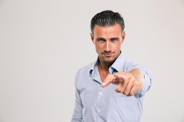 Retrato de um empresário confiante apontando o dedo para a câmera no espaço cinza