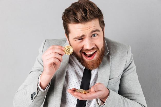 Retrato de um empresário confiante mostrando bitcoins dourados