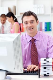 Retrato de um empresário confiante trabalhando em seu computador
