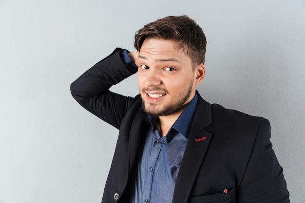 Retrato de um empresário confuso, arranhando a cabeça