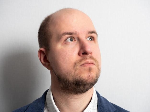 Retrato de um empresário do sexo masculino, caucasiano, de fato, olhando pensativamente para longe. retrato vertical, fundo claro, pelos faciais. careca