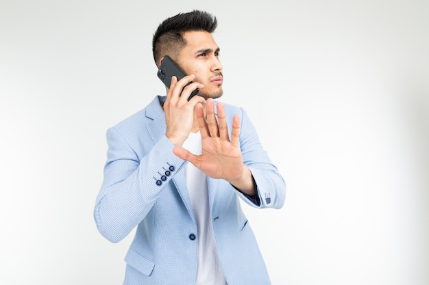 Retrato de um empresário em um casaco azul falando seriamente com os parceiros no telefone