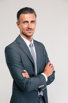 Retrato de um empresário feliz em pé com os braços cruzados isolados