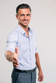 Retrato de um empresário feliz esticando a mão para um aperto de mão no espaço cinza