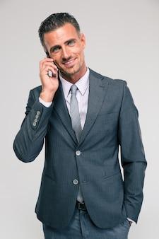 Retrato de um empresário feliz falando ao telefone isolado
