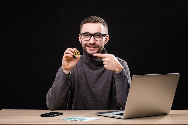 Retrato de um empresário feliz mostrando bitcoin enquanto está sentado na mesa com um laptop isolado sobre o preto