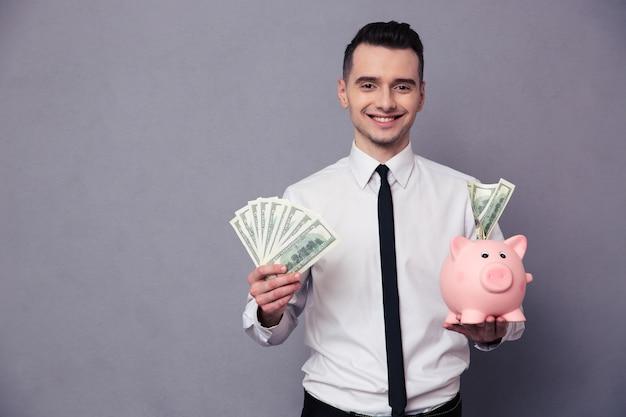 Retrato de um empresário feliz segurando um cofrinho de porco e dinheiro na parede cinza
