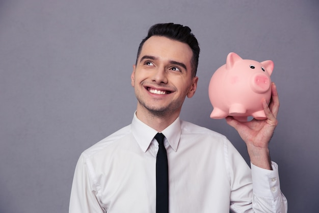 Retrato de um empresário feliz segurando um mealheiro de porco na parede cinza