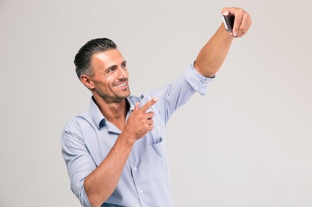 Retrato de um empresário feliz tirando foto de selfie em smartphone isolado