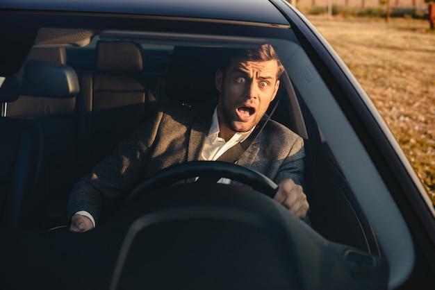 Retrato de um empresário gritando quase batendo carro