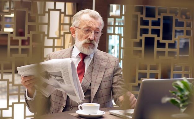 Retrato de um empresário idoso, um velho de óculos e um elegante terno formal, sentado em uma cadeira no escritório