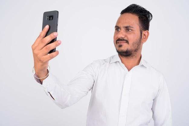 Retrato de um empresário indiano barbudo tirando uma selfie com o telefone