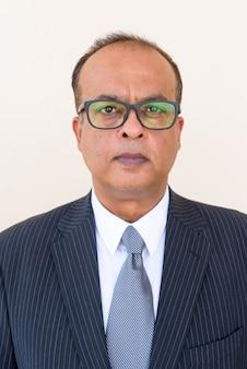 Retrato de um empresário indiano usando óculos contra uma parede simples ao ar livre