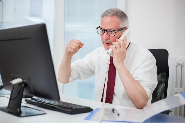 Retrato de um empresário irritado, gritando no telefone