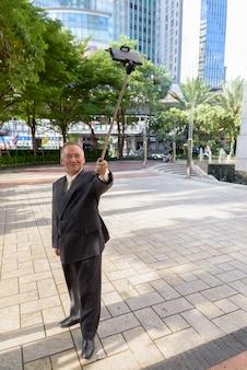 Retrato de um empresário japonês maduro de terno explorando a cidade de bangkok