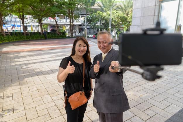 Retrato de um empresário japonês maduro e uma mulher japonesa madura explorando a cidade de bangkok