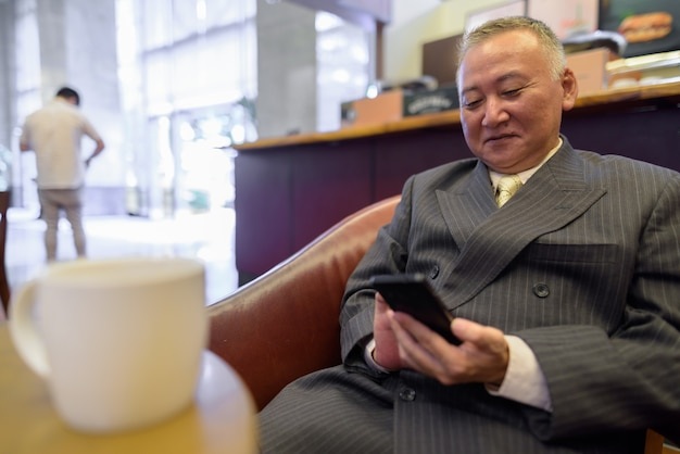 Retrato de um empresário japonês maduro relaxando dentro de uma cafeteria