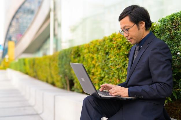 Retrato de um empresário japonês pegando ar fresco com a natureza ao ar livre da cidade