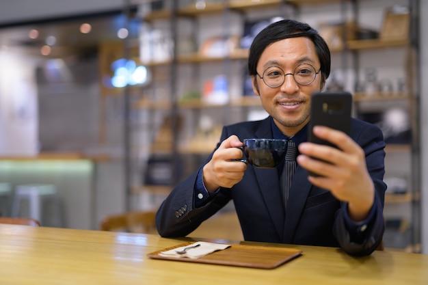 Retrato de um empresário japonês sentado dentro de uma cafeteria
