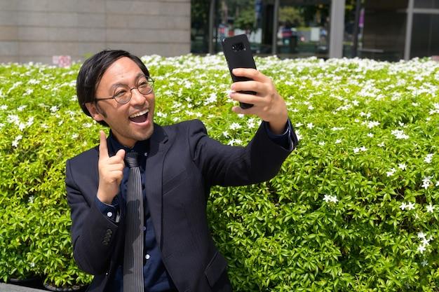 Retrato de um empresário japonês tomando ar fresco com a natureza na cidade