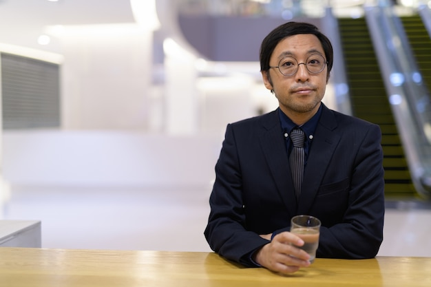 Retrato de um empresário japonês trabalhando dentro de um prédio comercial