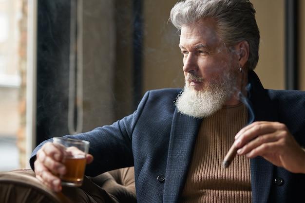 Retrato de um empresário maduro barbudo segurando um charuto e um copo de uísque enquanto relaxa