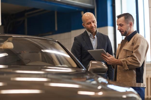 Retrato de um empresário maduro conversando com um mecânico enquanto verifica o carro de luxo na inspeção anual, copie o espaço