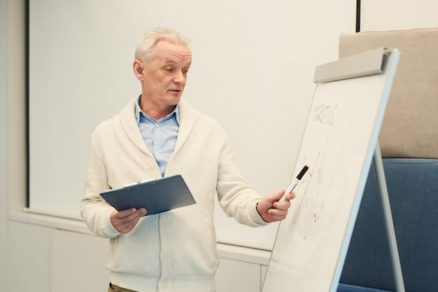 Retrato de um empresário moderno de cabelos brancos ao lado da mesa na sala de conferências enquanto faz uma apresentação ou seminário.