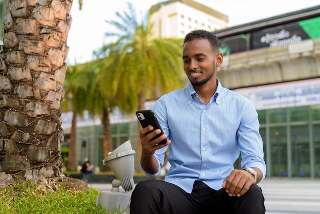 Retrato de um empresário negro africano bonito ao ar livre na cidade durante o verão, sentado e usando o telefone celular, sorrindo horizontalmente.