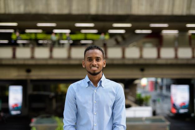 Retrato de um empresário negro africano bonito ao ar livre na cidade durante o verão, sorrindo e olhando para a câmera