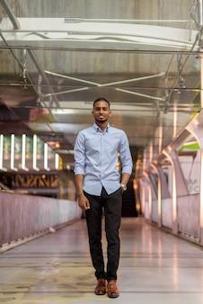 Retrato de um empresário negro africano bonito caminhando ao ar livre na cidade à noite, em pé na passarela vertical, corpo inteiro.