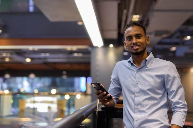 Retrato de um empresário negro africano bonito dentro de um shopping, sorrindo e segurando um celular na horizontal.