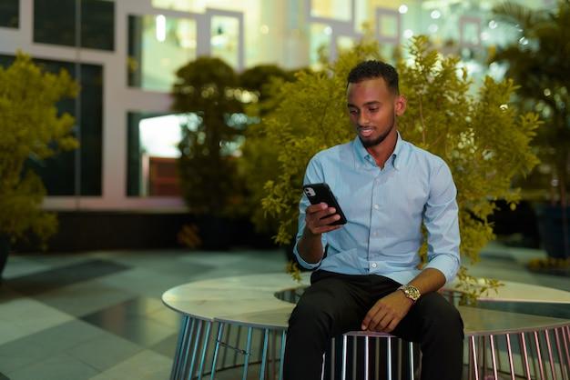 Retrato de um empresário negro africano bonito sentado ao ar livre na cidade à noite, enquanto usa a foto horizontal do telefone celular