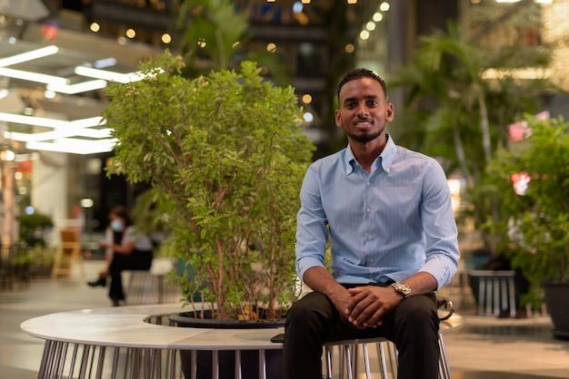 Retrato de um empresário negro africano bonito sentado ao ar livre na cidade à noite, horizontal.