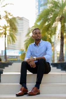Retrato de um empresário negro africano bonito sentado ao ar livre na cidade durante o verão, pensando em uma foto vertical