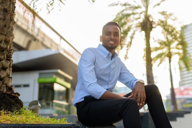Retrato de um empresário negro africano bonito sentado ao ar livre na cidade durante o verão, sorrindo, tiro horizontal