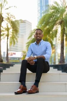 Retrato de um empresário negro africano bonito sentado ao ar livre na cidade durante o verão, sorrindo, tiro vertical