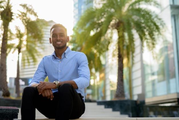 Retrato de um empresário negro africano bonito sentado ao ar livre na cidade durante o verão.