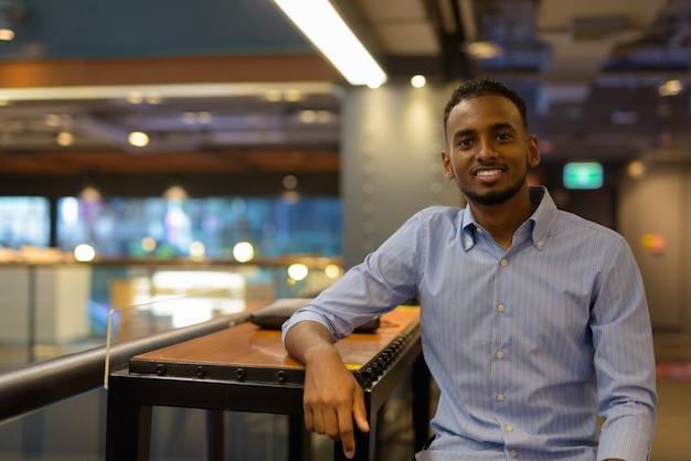 Retrato de um empresário negro africano bonito sentado dentro de um shopping enquanto sorri na horizontal.