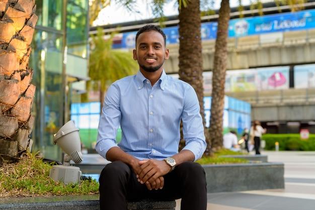 Retrato de um empresário negro africano bonito sentado e sorrindo ao ar livre na cidade durante o verão horizontal.