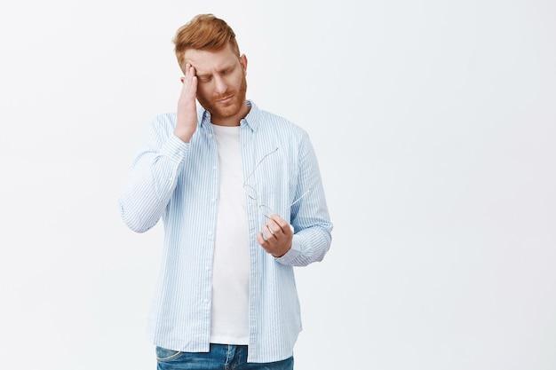 Retrato de um empresário ruivo exausto e sombrio em uma camisa azul casual, esfregando a têmpora, tirando os óculos, trabalhando demais, sofrendo de dor de cabeça na parede cinza