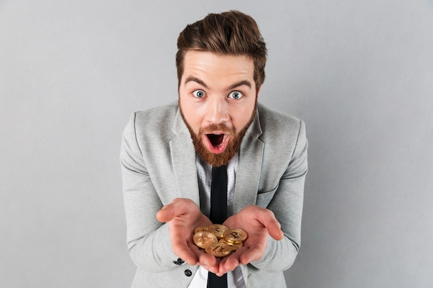 Retrato de um empresário satisfeito mostrando bitcoins dourados
