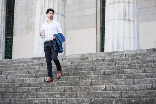 Retrato de um empresário segurando uma xícara de café a caminho de trabalhar ao ar livre. conceito de negócios.