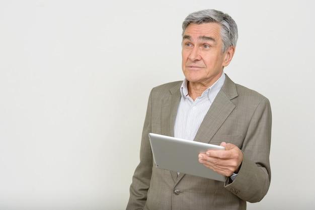 Retrato de um empresário sênior bonito pensando enquanto usa o tablet digital