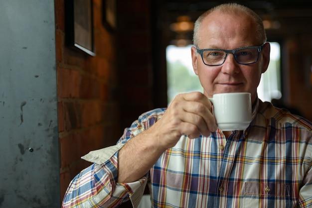 Retrato de um empresário sênior tomando café na cafeteria