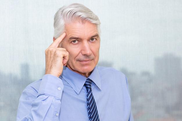 Retrato de um empresário sério apontando para a cabeça