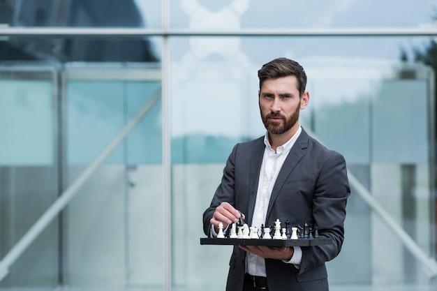 Retrato de um empresário sério de sucesso segurando um tabuleiro com o xadrez nas mãos e se oferecendo para dar um passo