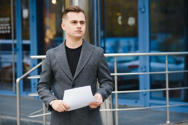 Retrato de um empresário sério procurando jornais em ruas da cidade